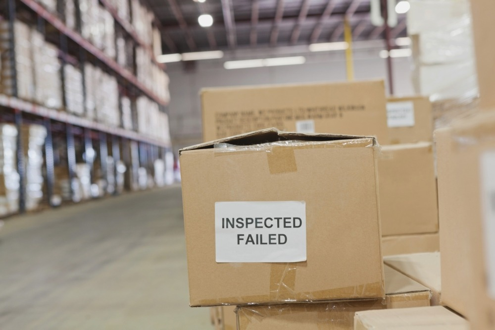 ETQ Reliance nonconformance return material authorization boxes in warehouse with inspection failed sticker on box