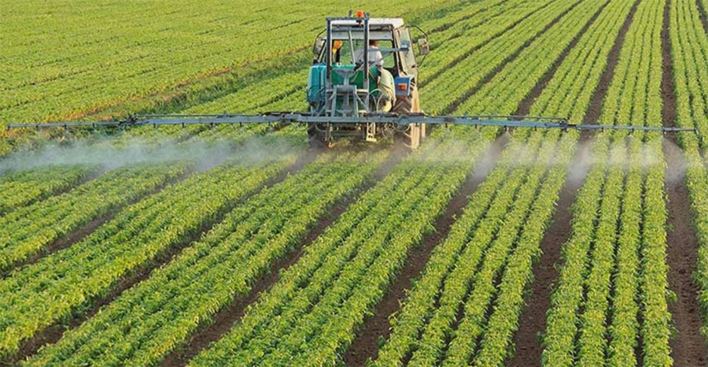 ETQ Reliance Quality Management for Chemical and Agrisciences in field with large tractor spraying chemicals