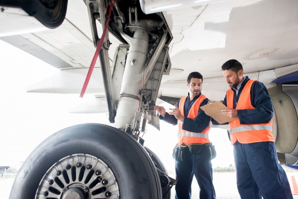 etq reliance aviation safety management employees inspecting plane on tarmac