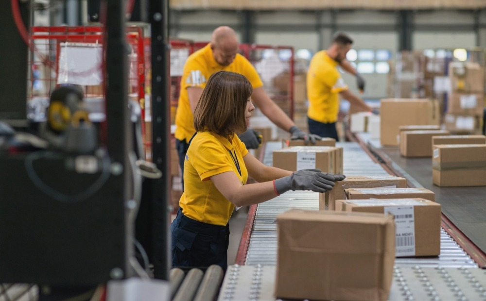 Employees on assembly line inspecting boxes