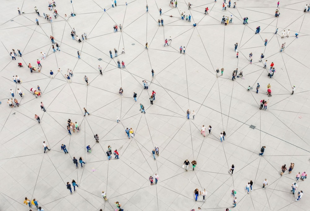 Aerial view of people walking around connected with lines to convey a network