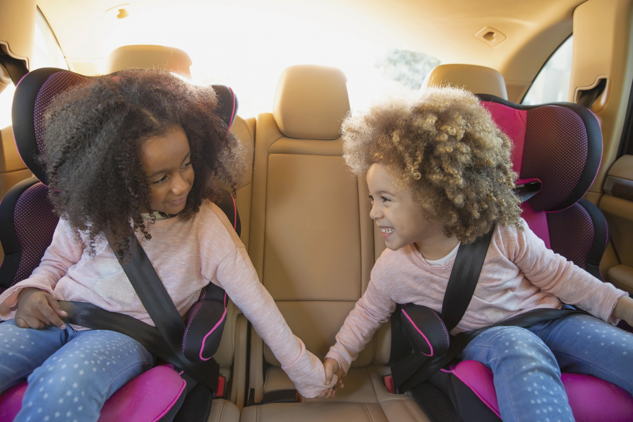 Two little girls in child seats holding hands and smiling in back seat of car