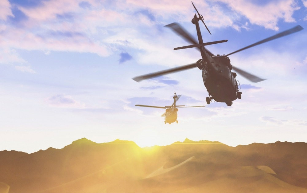 Two Aerospace defense helicopters flying over desert