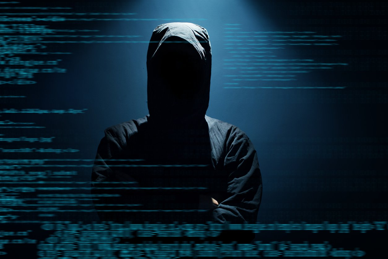 Potential hooded hacker wearing all black with binary background