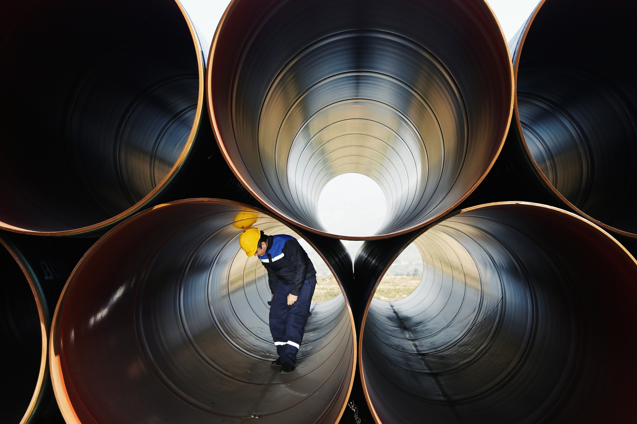 A man inspecting industrial pipes