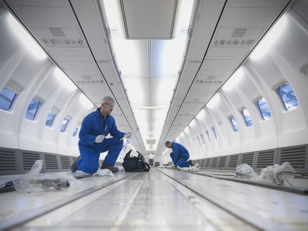 Two aviation assemblers building the interior of an airplane fuselage